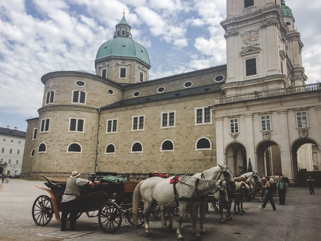 Beautiful Residenzplatz in the heart of Salzburg, with horse-drawn carriages and the Dom.